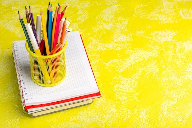 Lápis coloridos de vista frontal com caderno na superfície amarela