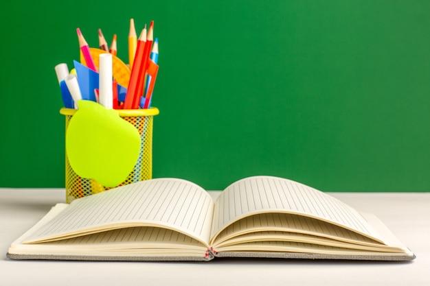 Lápis coloridos de vista frontal com caderno na superfície verde