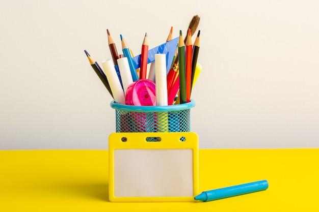 Lápis coloridos diferentes de vista frontal com canetas hidrográficas na mesa amarela