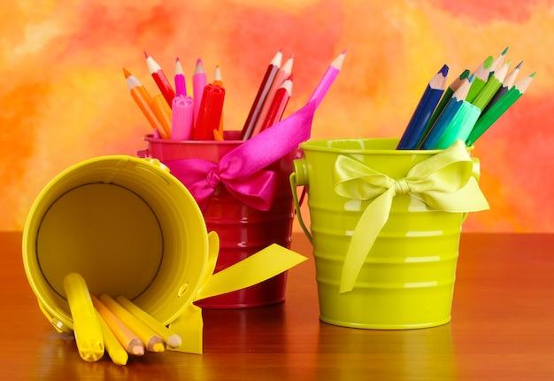 Lápis coloridos e canetas hidrográficas em baldes coloridos