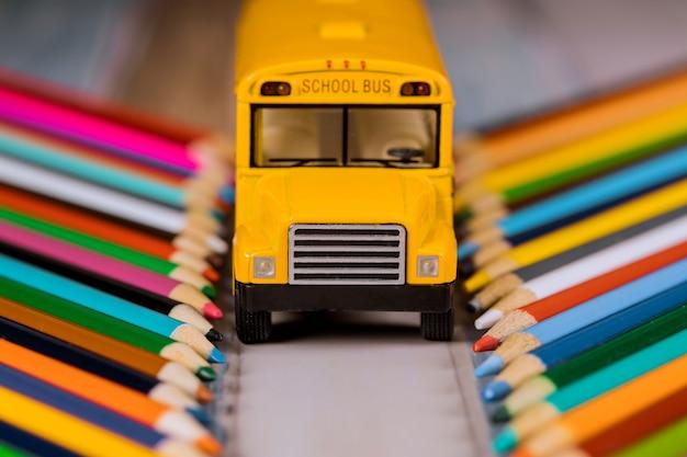 Lápis coloridos e ônibus escolar amarelo, de volta à escola.