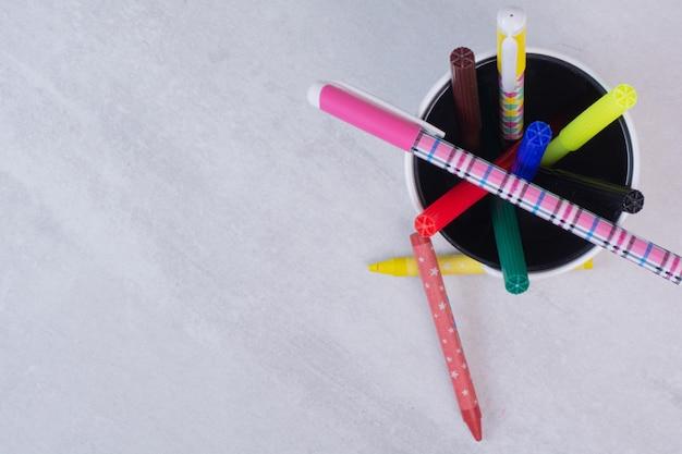 Lápis coloridos em estojo na mesa branca.