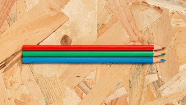 Lápis coloridos em fundo de madeira