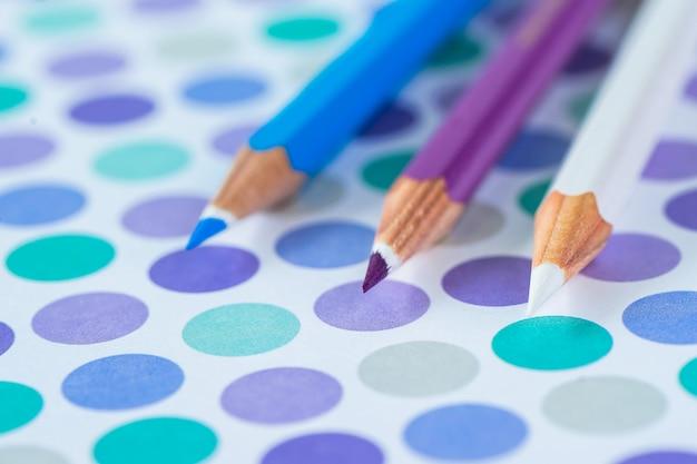 Lápis coloridos em um fundo pastel a um ponto com espaço para o texto.
