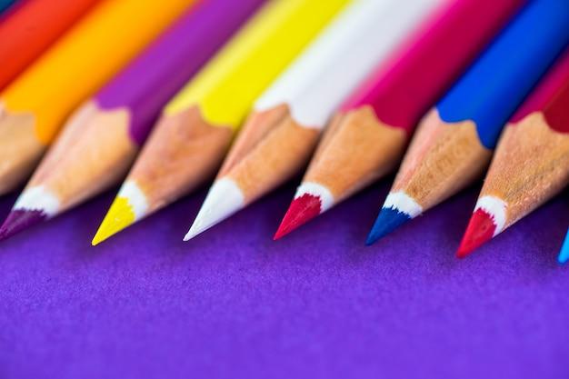 Lápis coloridos em um fundo violeta com espaço para o texto.