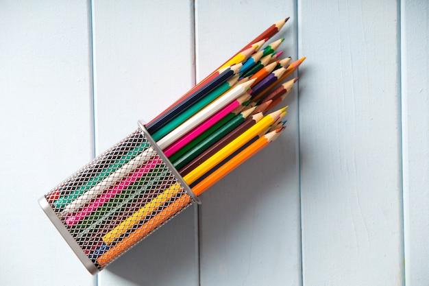 Lápis coloridos na mesa de madeira branca