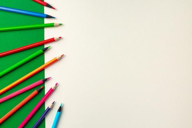 Lápis coloridos na vista superior do fundo do papel verde e branco
