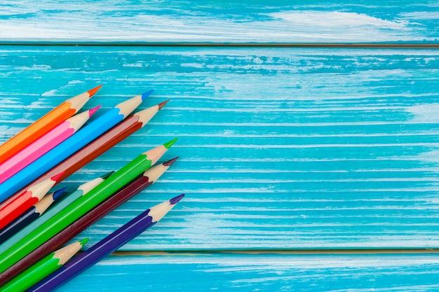 Lápis coloridos sobre um fundo azul de madeira brilhante