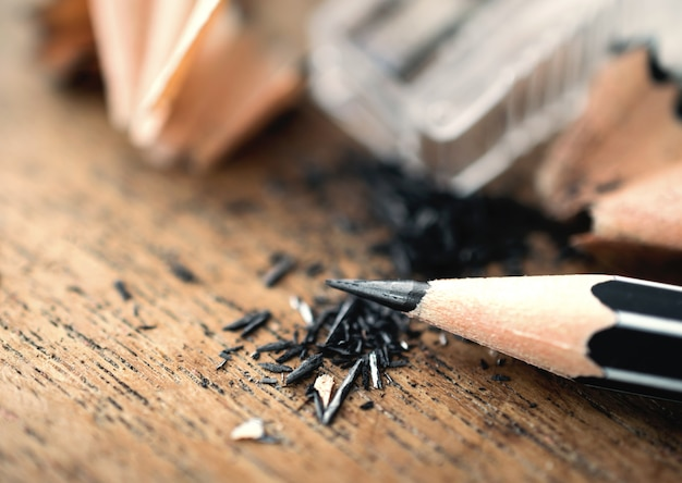 Lápis com aparas de afiar, na mesa de madeira ..