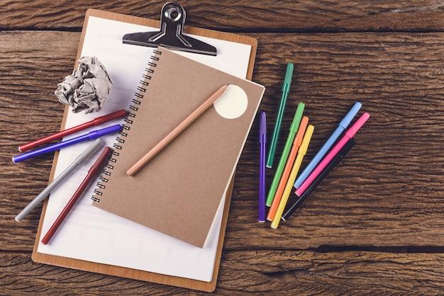 Lápis com caderno e cores mágicas no fundo de madeira. conceito de educação e ideia