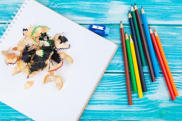 Lápis, cortes de lápis e papel em branco em uma mesa de mesa