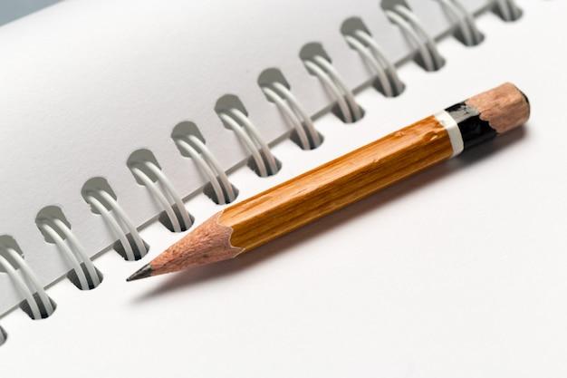 Lápis curto com o bloco de notas na mesa cinza