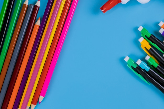 Lápis da cor isolado no fundo azul, conceito da arte da educação.