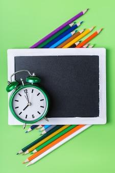 Lápis de arco-íris coloridos e despertador em fundo verde-limão