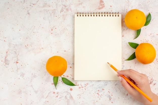 Lápis de bloco de notas de mandarinas frescas de vista superior em mão feminina em superfície brilhante isolada com espaço livre