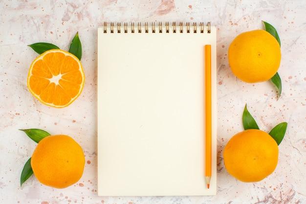 Lápis de bloco de notas de mandarinas frescas de vista superior na superfície isolada brilhante