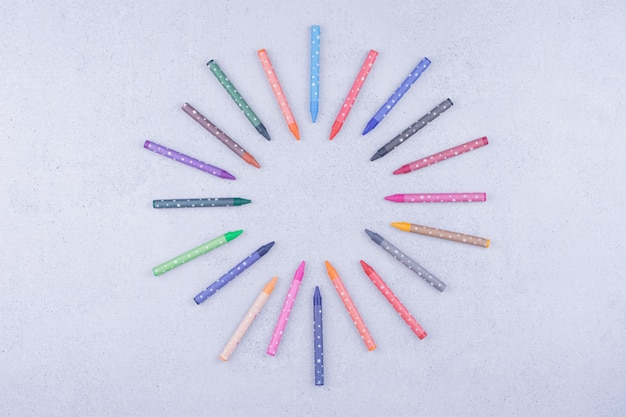 Lápis de cera coloridos isolados em superfície cinza