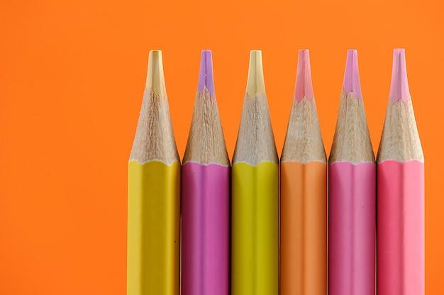 Lápis de cera coloridos organizados em uma linha sobre um fundo laranja brilhante