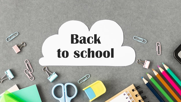Lápis de cera e texto de volta às aulas sobre mesa cinza