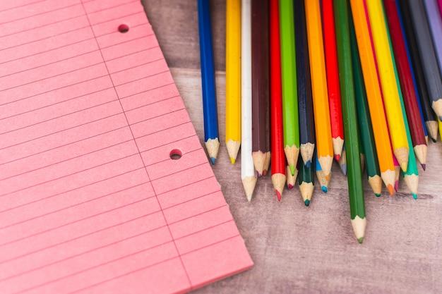 Lápis de cor ao lado de cadernos sobre uma mesa
