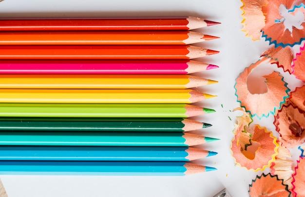 Lápis de cor, aparas e um apontador. acessórios escolares