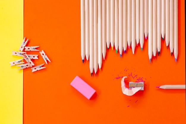 Lápis de cor, apontador e apagador copiam espaço, vista alta