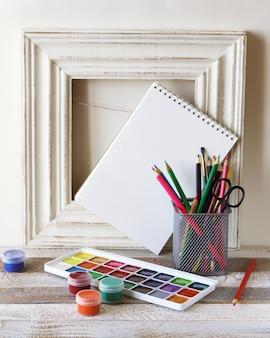 Lápis de cor, aquarelas e caderno em branco no fundo de uma moldura de madeira