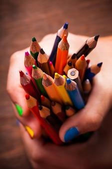 Lápis de cor arco-íris e mãos de adolescente com unhas multicoloridas