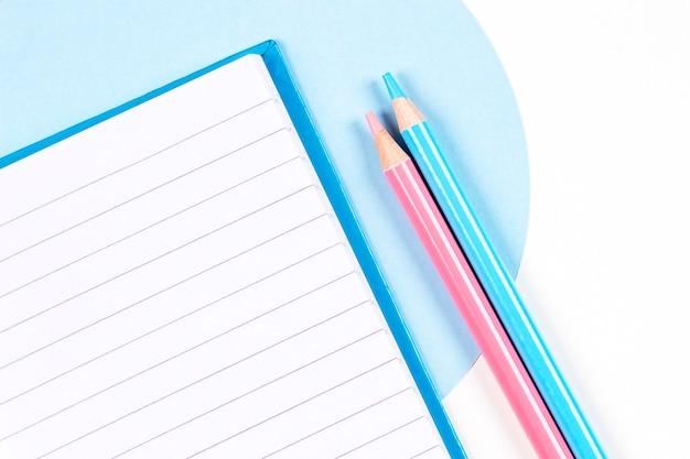 Lápis de cor azul claro e rosa com caderno aberto na vista superior geométrica de fundo azul e branco
