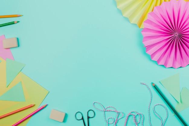 Lápis de cor; borracha; papel; tesoura; corda e papel circular sobre fundo azul
