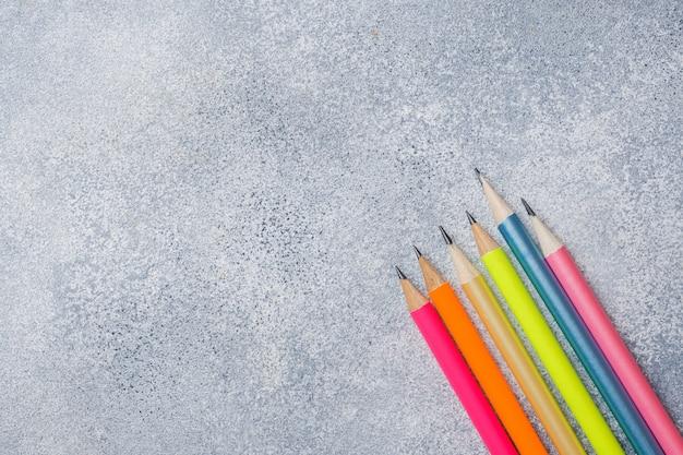 Lápis de cor brilhantes sobre o fundo cinza
