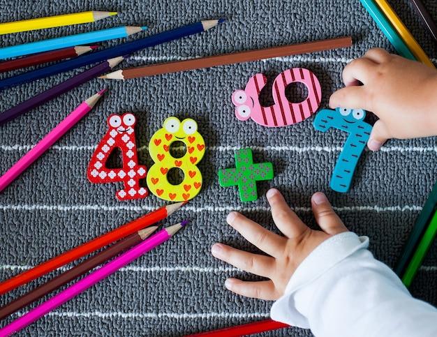 Lápis de cor coloridos e figura com mãos de criança pequena. plano de fundo pré-escolar e do jardim de infância. de volta ao conceito de escola.
