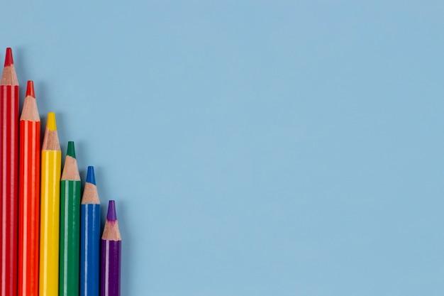 Lápis de cor com as cores do arco-íris da bandeira do orgulho gay lgbt dispostos na vista superior do plano de fundo azul claro