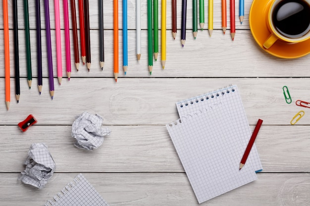 Lápis de cor com o bloco de notas e papel amassado na mesa branca com uma xícara de café amarela