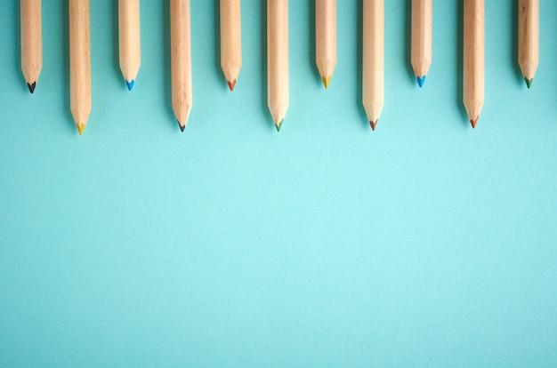 Lápis de cor de madeira em fundo azul com copyspace, lay plana