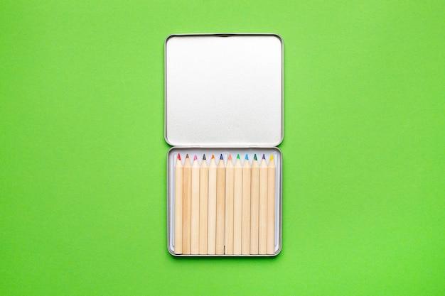 Lápis de cor de madeira em uma caixa de metal verde