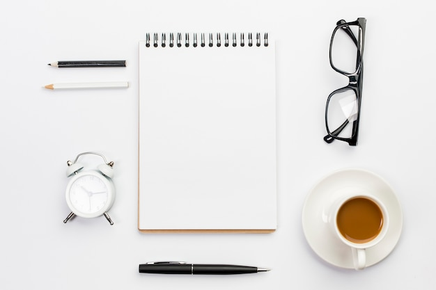 Lápis de cor, despertador, caneta, óculos e bloco de notas em espiral com uma xícara de café em pano de fundo branco
