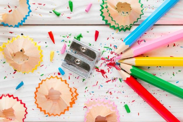 Lápis de cor e apontador em um fundo branco de madeira