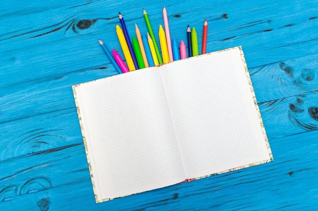 Lápis de cor e bloco de notas. conceito de escola