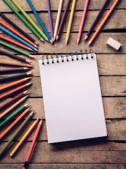 Lápis de cor e caderno em fundo madeira.