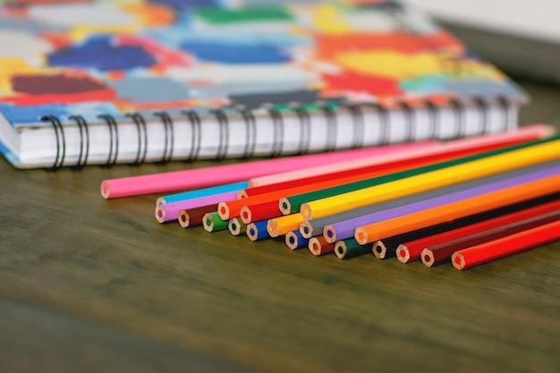 Lápis de cor e caderno na mesa de madeira
