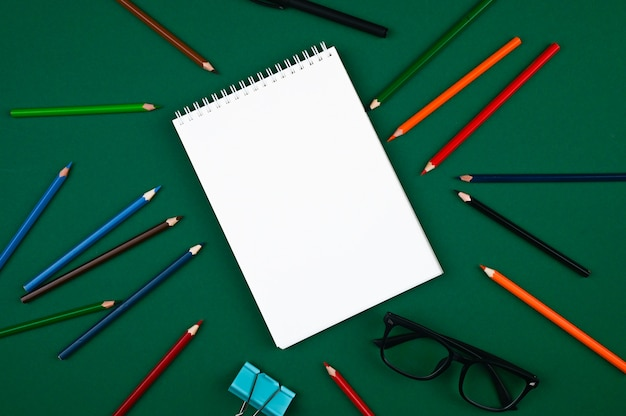 Lápis de cor e óculos perto do caderno vazio.