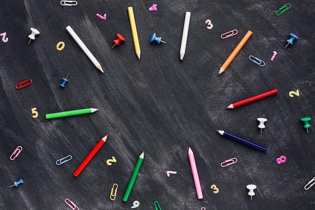 Lápis de cor e pinos com clipes de papel espalhados no quadro-negro