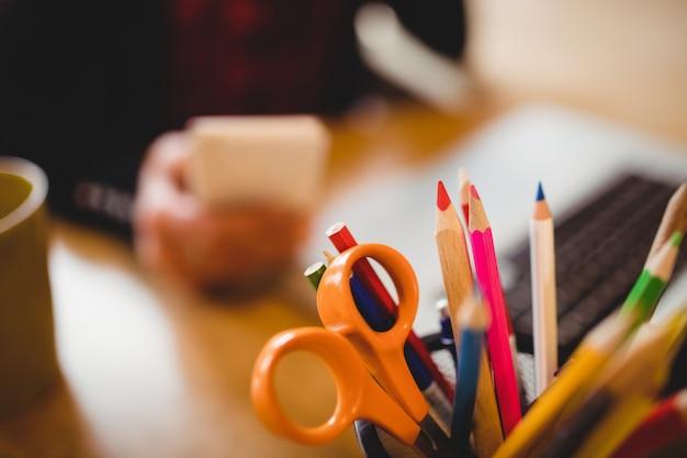 Lápis de cor e tesoura no porta-canetas