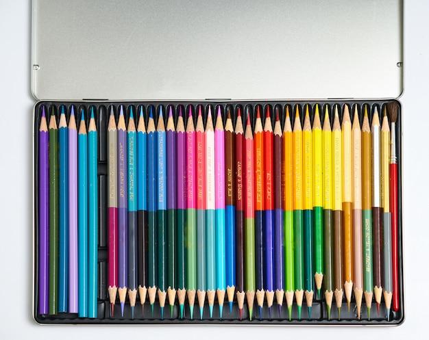 Lápis de cor em caixa de alumínio no fundo branco isolado