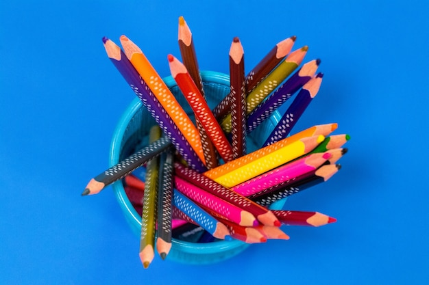 Lápis de cor em um estojo sobre fundo azul, vista superior.