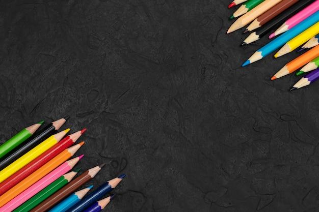 Lápis de cor em um plano de fundo texturizado preto.