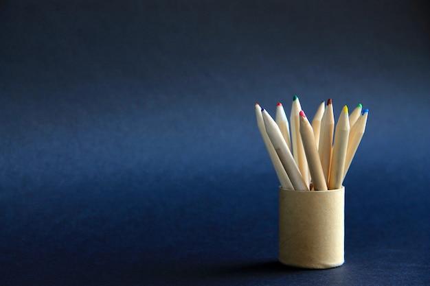 Lápis de cor em uma caixa de papelão em um fundo escuro