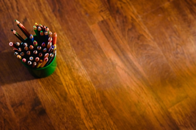 Lápis de cor em uma caneta cheia, no chão com fundo de madeira quente e espaço livre para texto