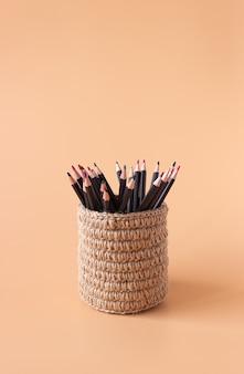 Lápis de cor em uma cesta de vime feita de juta em bege